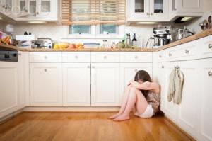 Teenage girl sitting on the kitchen floor looking sad