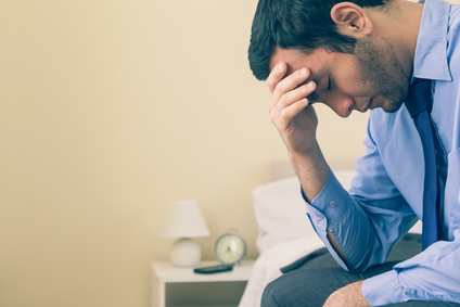 Sad man sitting head in hands on his bed in a bedroom at home