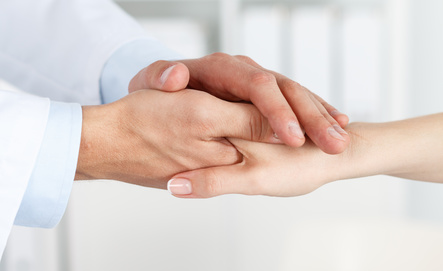 Friendly male doctor's hands holding female patient's hand